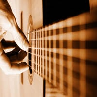 Acoustic guitar player closeup with focus on the hand