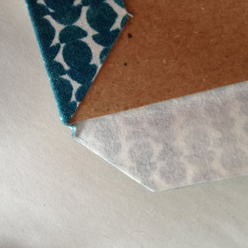 Fold the cloth around the corner of the book board