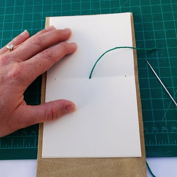 Leave a small length of thread on the inside of the signature