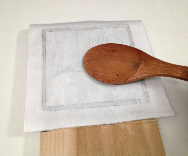 lightly rub the back of the paper with the rice spoon