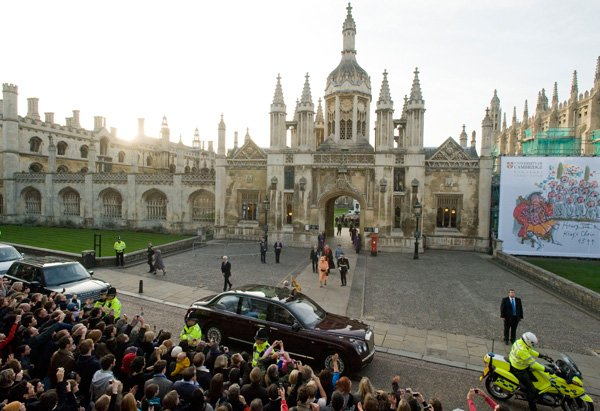 A different, wide perspective shows the Queen leaving Cambridge University to crowds of people.