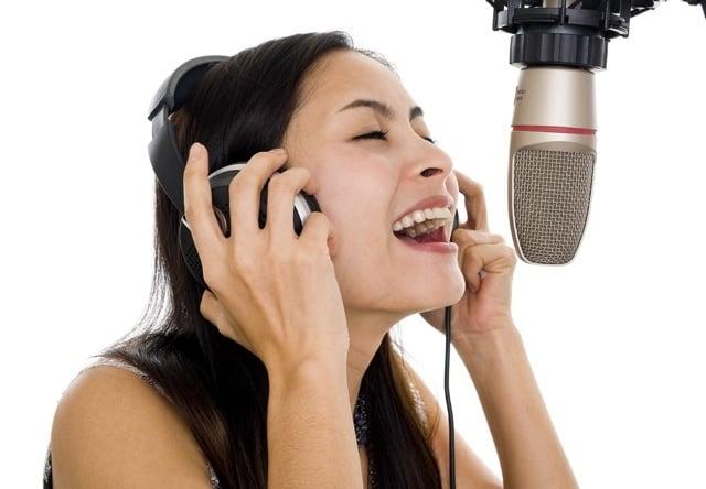 Female vocalist wearing headphones while recording in the studio. Image: PhotoDune.