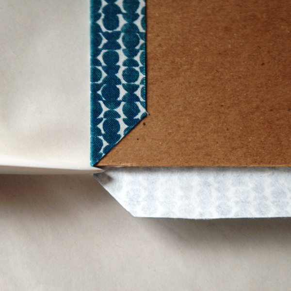 Fold the cloth around the corner of the book board