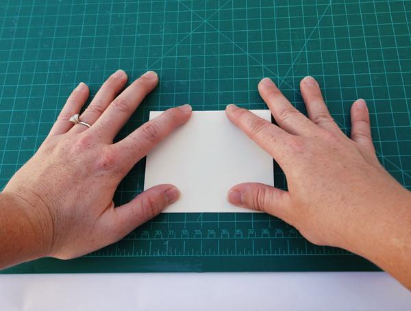 Pegue uma folha de papel a partir de seu bloco de texto e dobre-o ao meio transversalmente.