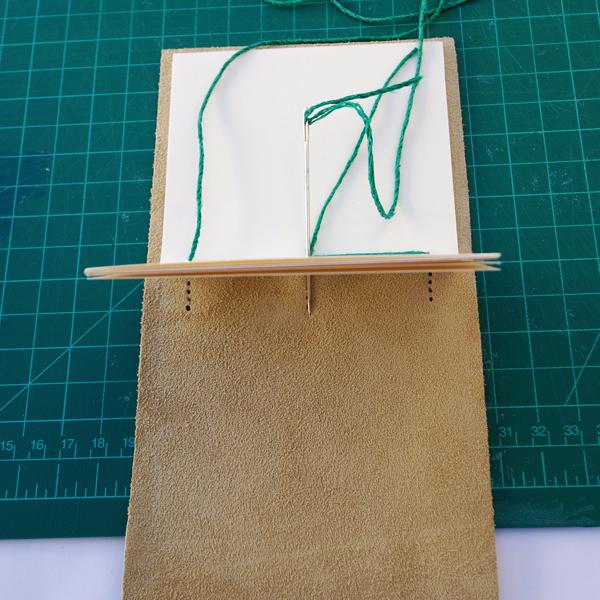 costurar para fora através do furo n º 2, pela terceira vez, mas não costurar através do couro.