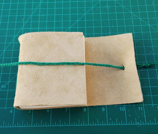 Empurrar uma extremidade da trança através da fenda e fazer um nó.