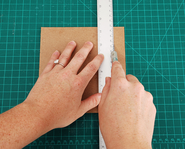 score a line along three sides measuring one book thickness away from the edge