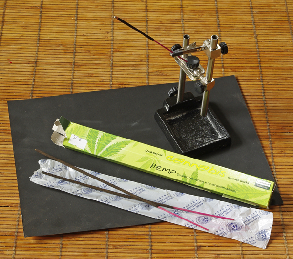 incense sticks and a a third hand device on a plastic base
